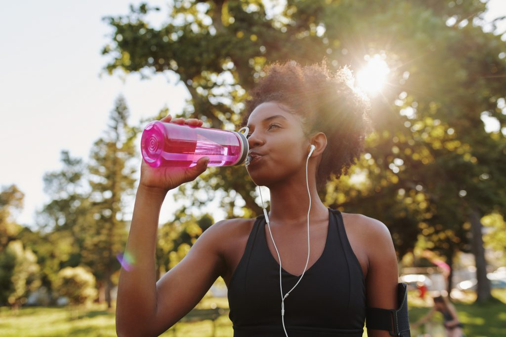 Fitness athlete young african american woman listening to music on earphones drinking water in a reusable water bottle.