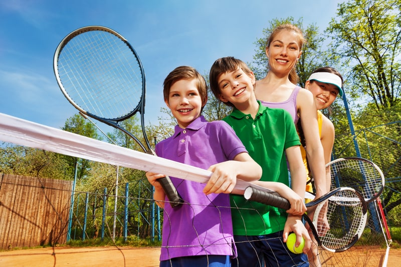 Family of tennis players standing next to the net